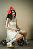 Lonely woman in the role of doll sitting on bicycle Stock Image