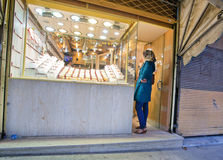 Lonely woman selects gold ornaments in store of jeweler in Middle East Royalty Free Stock Image