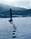 Lonely woman silhouette at winter mountains. Footprints on the snow, enjoying wintertime nature view,one girl walking outdoor Stock Photo
