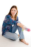 Lonely woman siting on the flor with flowers in ha Stock Images