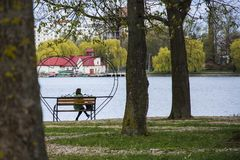 Lonely woman sitting alone on a bench in a pack near the lake. 2018 Stock Image