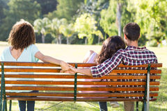 Lonely woman sitting with couple in park Stock Images
