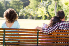 Lonely woman sitting with couple in park Royalty Free Stock Photos