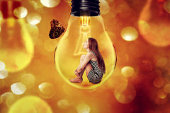 Lonely woman sitting inside light bulb looking at butterfly. Isolated on defocused bokeh background. Dreamland space station Royalty Free Stock Image