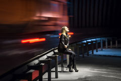 Lonely woman sitting at night at highway with cars rushing past. Lonely sad woman sitting at night at highway with cars rushing past her stock photography