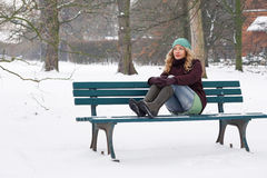 Lonely woman sitting on park bench in winter Royalty Free Stock Images