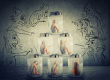 Lonely woman sitting in a pile of glass jars surrounded by angry negative evil men Stock Photos