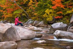 Lonely woman sitting on a rock along a mountain river in autumn