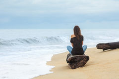 Lonely woman sitting on the tropical beach. By the sea royalty free stock photography
