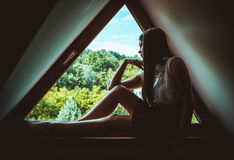 Lonely woman sitting on a window. Young lonely woman sitting on a window Royalty Free Stock Images