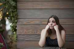 Lonely woman sitting in the wooden coffee shop Royalty Free Stock Image