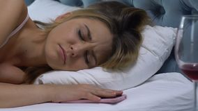 Lonely woman sleeping after drinking wine, smartphone lying near pillow, stress