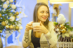 Lonely woman smiling and drinking coffee. In coffee shop with Christmas decorations Stock Image