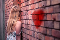 Lonely woman stand leaning against wall Stock Image