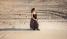 Lonely woman standing on sand dune Stock Image
