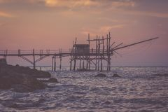 Lonely woman standing at trabocchi pier in nostalgic evening. Nostalgic evening at Adriatic sea. Lonely womant stands at trabocchi pier Stock Photo