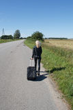 Lonely woman with suitcase. Go along rural roadside Stock Photography
