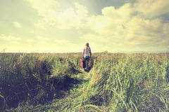 Lonely woman takes a trip to a different life. Lonely woman walking into infinity Royalty Free Stock Photography