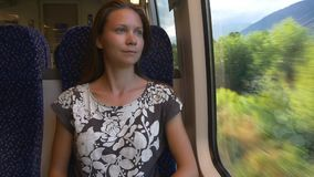 Lonely woman travels by train thinking of farewell. Sad mood. Farewell. Travelling by train in Alps. Pensive woman comfortably sitting by the window stock video footage