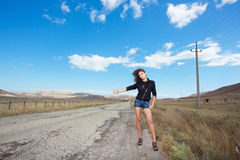 Lonely woman tries to stop the car on old road Stock Photo