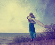 Lonely Woman in Turquoise Dress with Waving Scarf. Vintage Photo of Lonely Woman with Waving Scarf at the Sea. Toned Photo with Copy Space. Solitude Concept Royalty Free Stock Photos