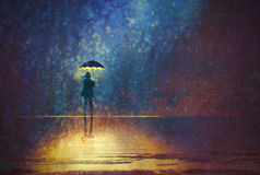 Lonely woman under umbrella lights in the dark Stock Photography