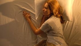 Lonely woman waking up and stroking sheet, remembering her husband, divorce