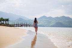 Lonely woman walk on sandy beach Stock Image
