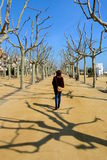 Lonely woman walking across a nice promenade on a sunny winter morning in Calella de la Costa, Maresme Seaside, Catalonia, Spain Stock Image