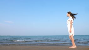 Lonely Woman walking along beach in white dress. Lovely girl walking along the beach in white dress stock video