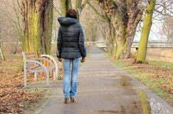 Lonely woman walking in park on cold rainy day Stock Photo