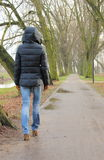 Lonely woman walking in park on cold rainy day Royalty Free Stock Image