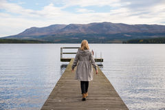 Lonely woman walking on a pier. With a lake and mountains in the background Stock Photos