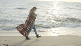 Lonely woman walking on the sandy beach with plaid. Young female spending time on the shore of the sea in cold day.
