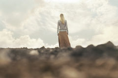 Lonely woman walking towards infinity in a surreal place Royalty Free Stock Image