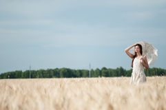 Lonely woman walking in wheat field. Timed. Stock Images