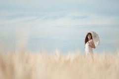 Lonely woman walking in wheat field. Timed. Royalty Free Stock Photography