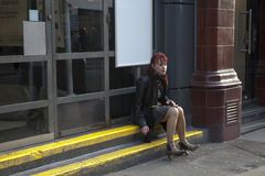 A lonely woman wears a short green skirt and a brown leather jacket, sits on the curb and smokes a cigarette. LONDON, ENGLAND - JULY 12, 2016 A lonely woman royalty free stock photography