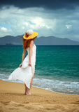 Lonely woman in a white dress standing at the sea Stock Photography