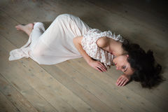 Lonely woman on wooden floor Stock Images