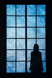 Lonely women looking at snowfall through big glass window Stock Images