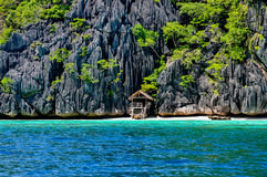 Lonely wooden bamboo house on stilts at a small. Lonely wooden bamboo hous on stilts at a small hidden beach on rocky island near Coron, Palawan, Philippines Stock Image