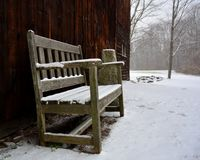 Lonely wooden bench in front of barn during snowstorm. Gray day brown bar snow covered stock photo