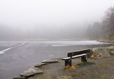 Lonely wooden bench in winter scenery by frozen lake in foggy rainy weather, bergen, norway Stock Photography