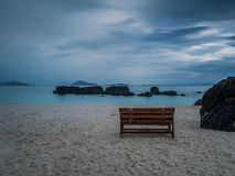 Lonely wooden chair on the beach after rain Stock Images