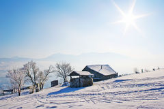 Lonely wooden house in mountains under blue sky. Lonely wooden house and trees in snow covered mountains under shiny blue sky Stock Photos