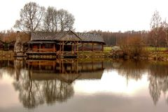 A lonely wooden hut on the shore of a pond stock image