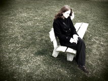 Lonely and Worried. A young lady sitting on a lonely bench by herself and worrying or being sad Royalty Free Stock Photo