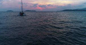 Lonely yacht, catamaran sailing on the sea at sunset going to the sun. stock video