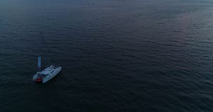 Lonely yacht, catamaran sailing on the sea to the sun at sunset. stock video